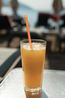 Glas orangensaft mit strohhalm