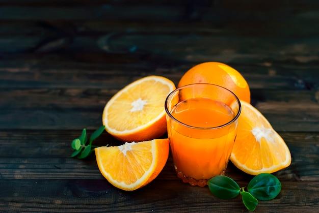 Glas orangensaft und eine gruppe orangen auf dunklem brett