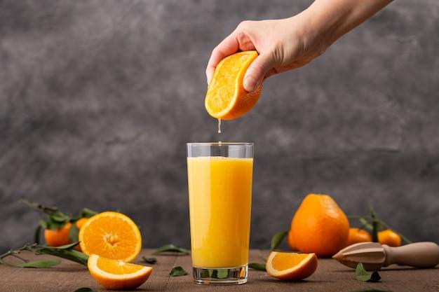 Glas orangensaft und eine person, die eine orange darin drückt