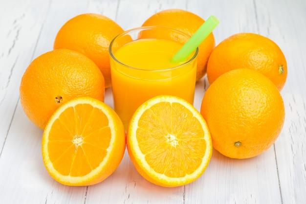 Glas orangensaft und orangen auf weißem tisch