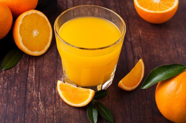 Glas organischer frischer orange smoothiesaft mit rohen orangen auf dunklem hölzernem hintergrund