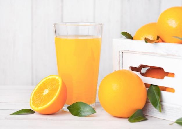 Glas organischer frischer orange smoothiesaft mit rohen orangen in der weißen holzkiste