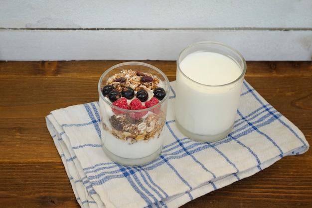 Glas reiner joghurt und joghurt mit müsli und obst. gesundes frühstück.