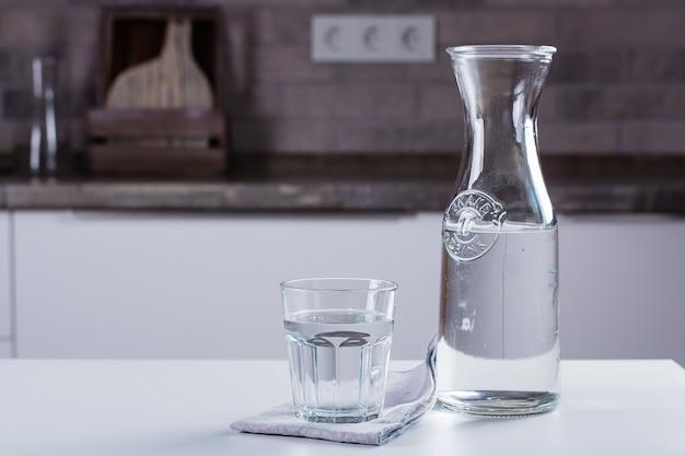 Glas reines wasser und flasche auf küchentisch. sauberes konzept