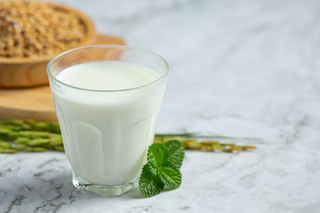 Glas reismilch mit reispflanze und reissamen auf weißem marmorboden