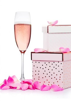 Glas rosa champagner mit herzen und rosa geschenkbox und stieg für valentinstag auf weißem hintergrund