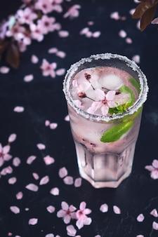 Glas rosa rosenchampagner, apfelwein oder limonade mit eis und minze und kirschblüten Premium Fotos