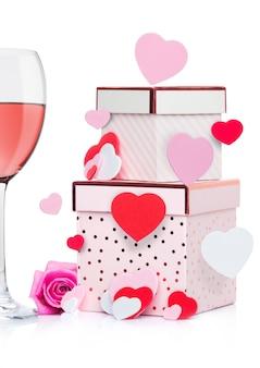 Glas rosa wein mit herzen und rosa geschenkbox und stieg für valentinstag auf weißem hintergrund mit fliegenherzen