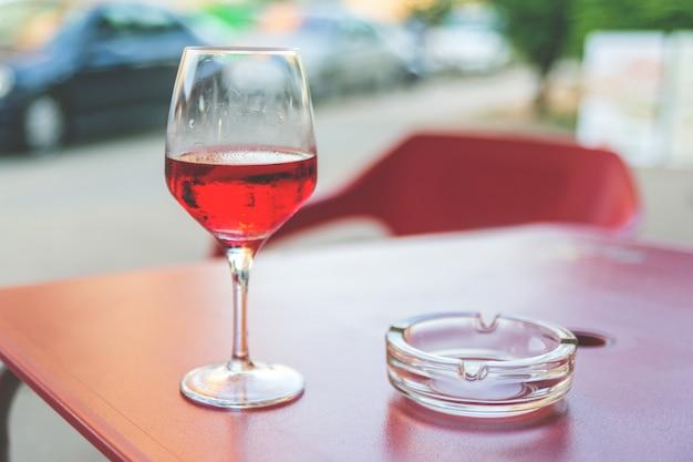 Glas rosafarbener wein auf dem tisch in der straßenkaffee weinlese, die selektiven fokus tont
