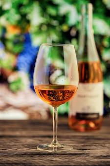Glas rosafarbener wein mit unscharfem weinberg