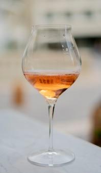 Glas roséwein am tisch vor dem restaurant. konzept des luxus