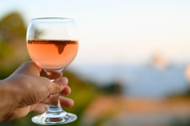 Glas roséwein in der hand einer frau gegen eine verschwommene seelandschaft