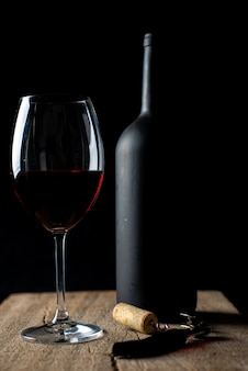 Glas rotwein auf dem rustikalen holztisch mit korkenzieher daneben und defokussierter weinflasche