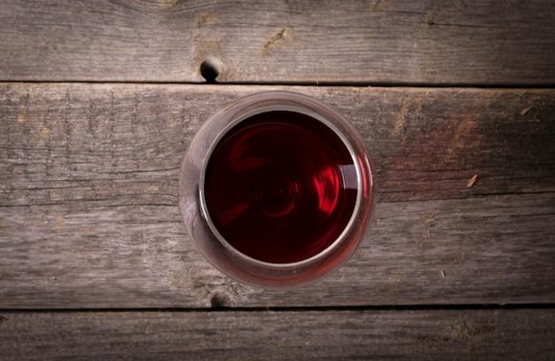 Glas rotwein auf holztisch. blick von oben