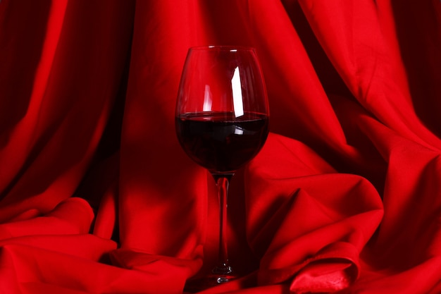 Glas rotwein auf rotem stoff
