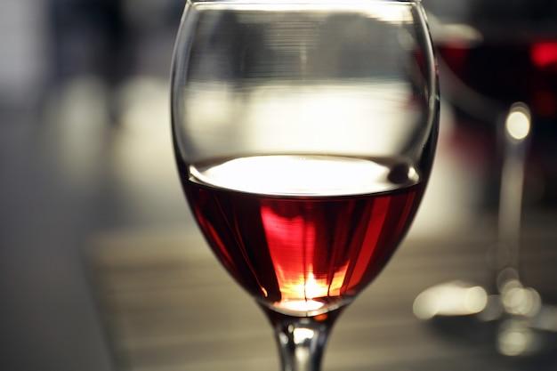 Glas rotwein auf unscharfem hintergrund