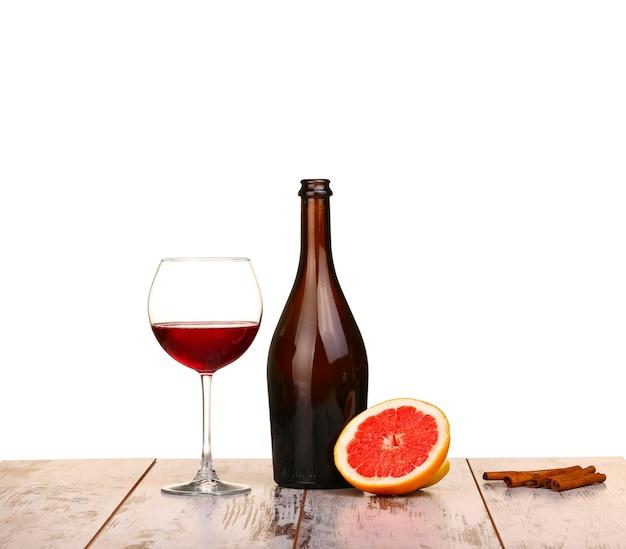 Glas rotwein, eine flasche wein und grapefruit an bord isoliert auf weiß