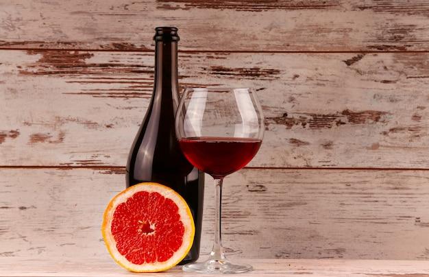 Glas rotwein, eine flasche wein und grapefruit auf den tabletten