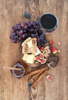 Glas rotwein, käsebrett, trauben, feige, erdbeeren, honig und brotstöcke auf rustikalem holztisch