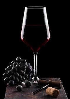 Glas rotwein mit dunklen trauben und vintage korkenzieheröffner und korken auf holzbrett auf schwarz