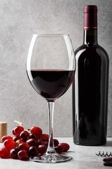 Glas rotwein mit flasche und trauben auf dem tisch.