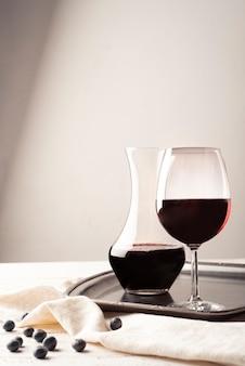 Glas rotwein mit karaffe auf einem tablett