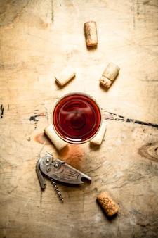 Glas rotwein mit korken und korkenzieher. auf hölzernem hintergrund.