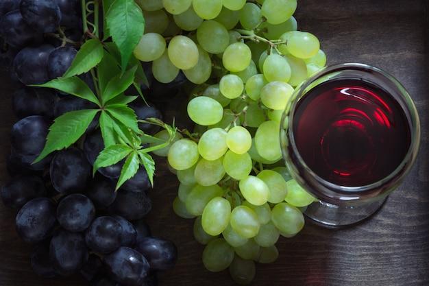Glas rotwein mit reifer traube auf hölzernem brett.