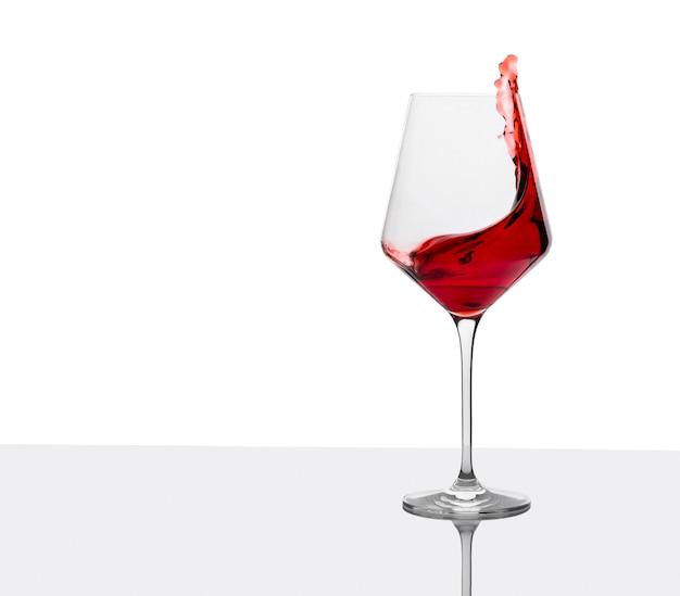 Glas rotwein mit spritzern auf weißem tisch.