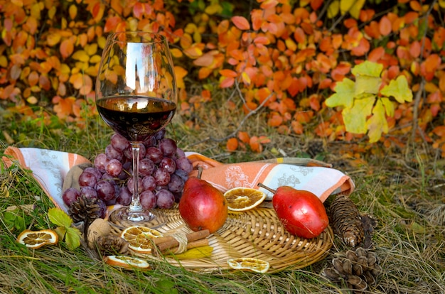 Glas rotwein mit trauben und birnen