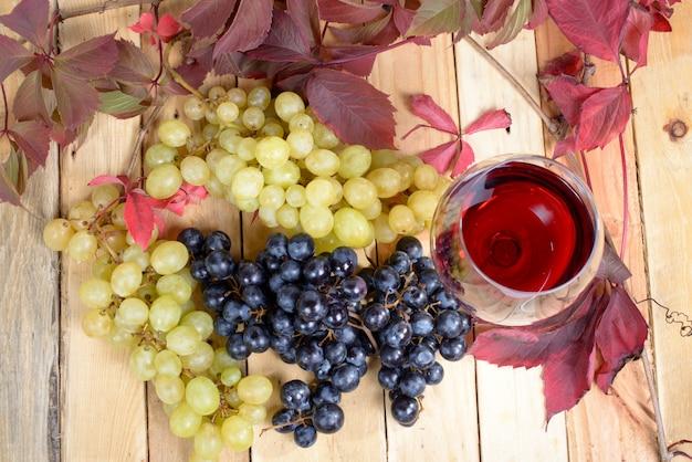 Glas rotwein mit vielen weintrauben