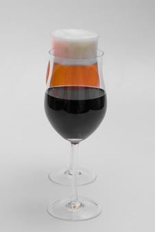 Glas rotwein und ein glas lagerbier auf weißem hintergrund.