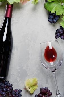 Glas rotwein und eine flasche trauben und weinblätter auf dem tisch
