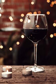 Glas rotwein und girlandenlichter