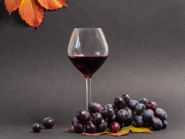 Glas rotwein und rote weintraube
