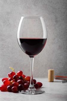 Glas rotwein und trauben auf dem tisch.