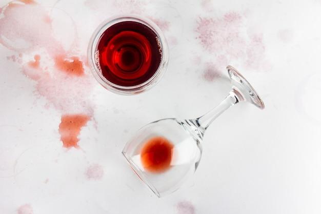 Glas rotwein und umgestürztes glas mit restwein auf weißem hintergrund, durchnässt und mit wein befleckt, ansicht von oben