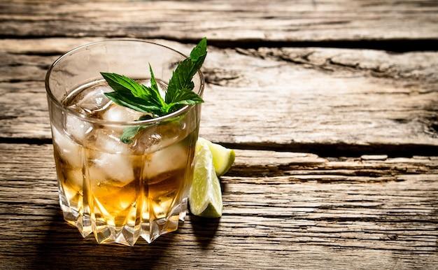 Glas rum mit eis, limette und minze.