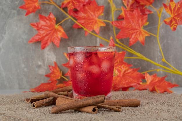 Glas saft mit fruchtscheiben, blättern und zimtstangen auf sackleinen
