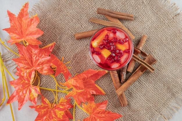 Glas saft mit fruchtscheiben und zimtstangen auf sackleinen