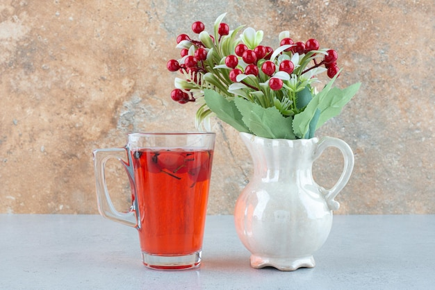 Glas saft mit hagebutten und künstlichen blumen auf blauem tisch.