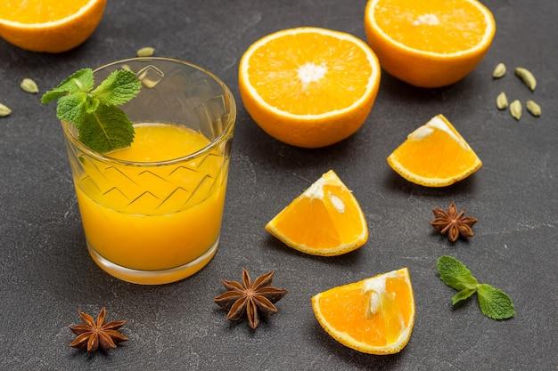 Glas saft mit minzblättern. sternanis und gehackte orangen auf dem tisch. schwarzer hintergrund. ansicht von oben