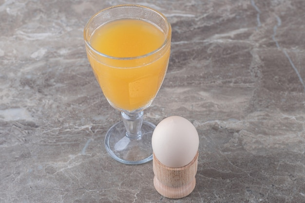 Glas saft und gekochtes ei auf marmortisch.