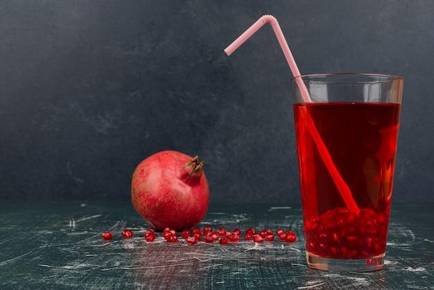 Glas saft und granatapfel auf marmortisch