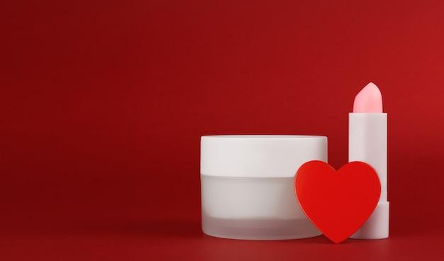 Glas sahne und lippenbalsam auf einem roten hintergrund mit herz. behälter für körperpflegebalsam.