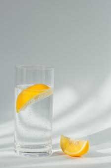 Glas sauberes mineral-sprudelwasser mit eis und zitrone auf weißem hintergrund mit sonnenschein. licht mit harten schatten und blendung aus dem glas. frühstück, frisches morgengetränk
