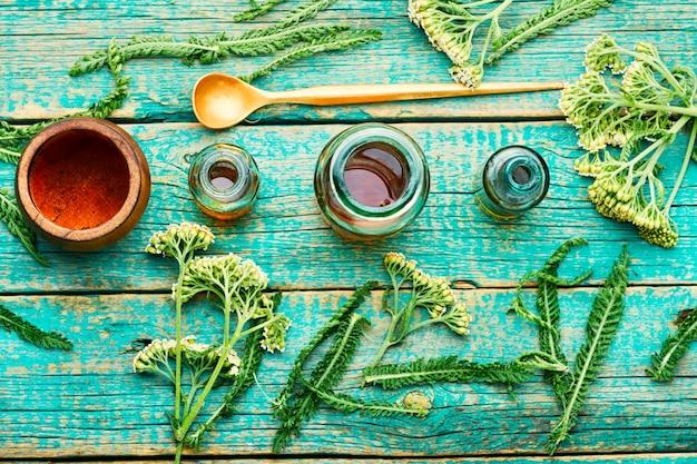 Glas schafgarbe tinktur. medizin aus heilkräutern auf holzhintergrund. kräuterkunde und homöopathie