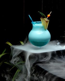 Glas schaumiger blauer cocktail, garniert mit ananasscheibe