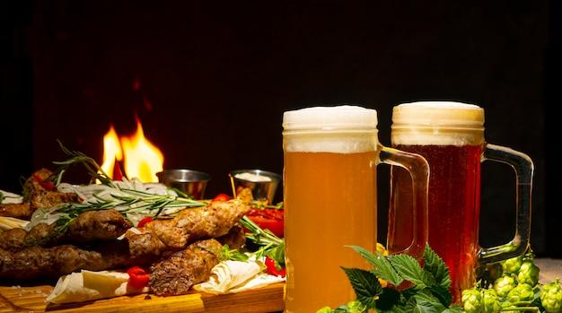 Glas schaumiges dunkles bier und helles bier auf einem hintergrund von gegrilltem fleisch und gemüse
