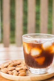 Glas schwarzer gefrorener kaffee mit mandelkorn
